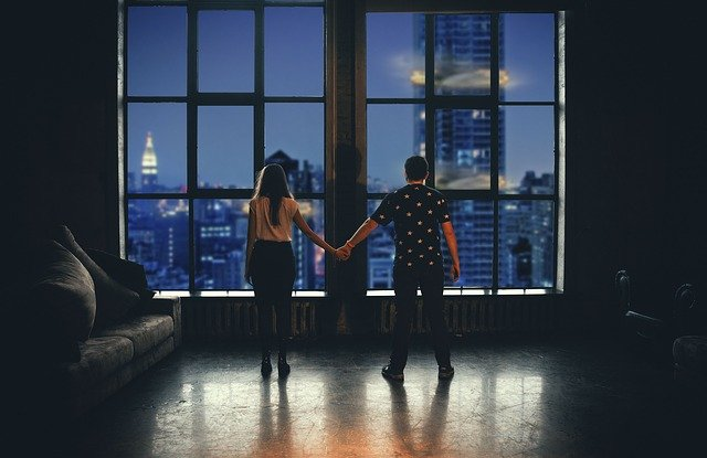 homem  e mulher de costas e de mãos dadas