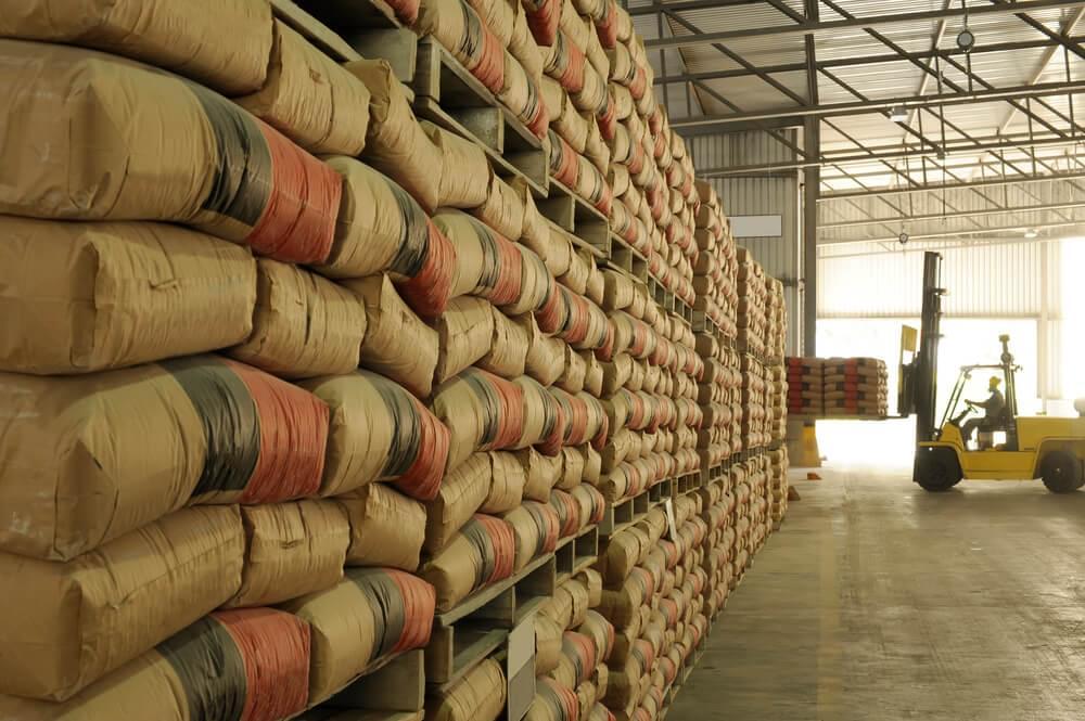 Imagem de galpão com estantes cheias de pilhas de sacos de cimento armazenados, usados na construção civil.