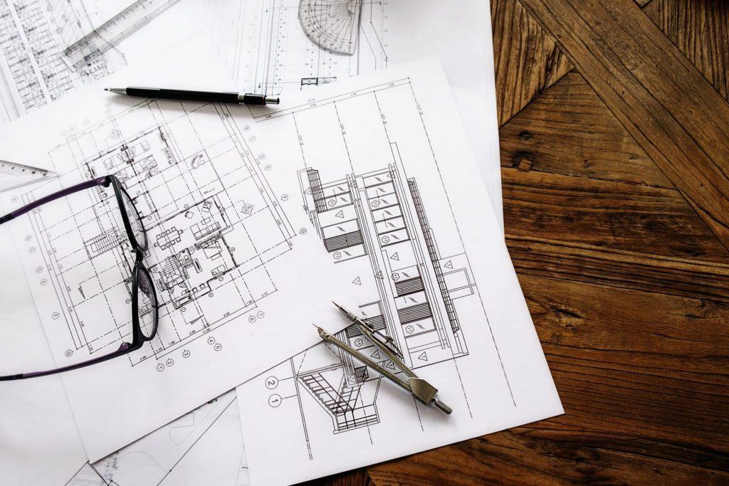 Óculos, compasso e lápis em cima de projetos.