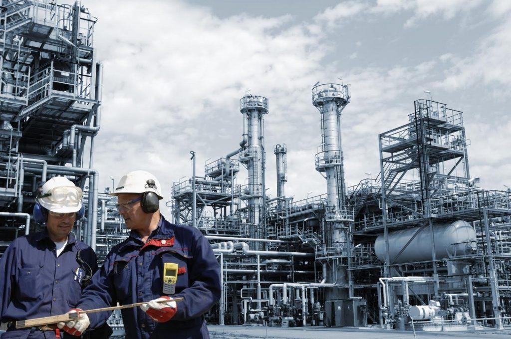 Engenheiros conversando próximo a tubulações de petróleo e gás representando áreas da engenharia