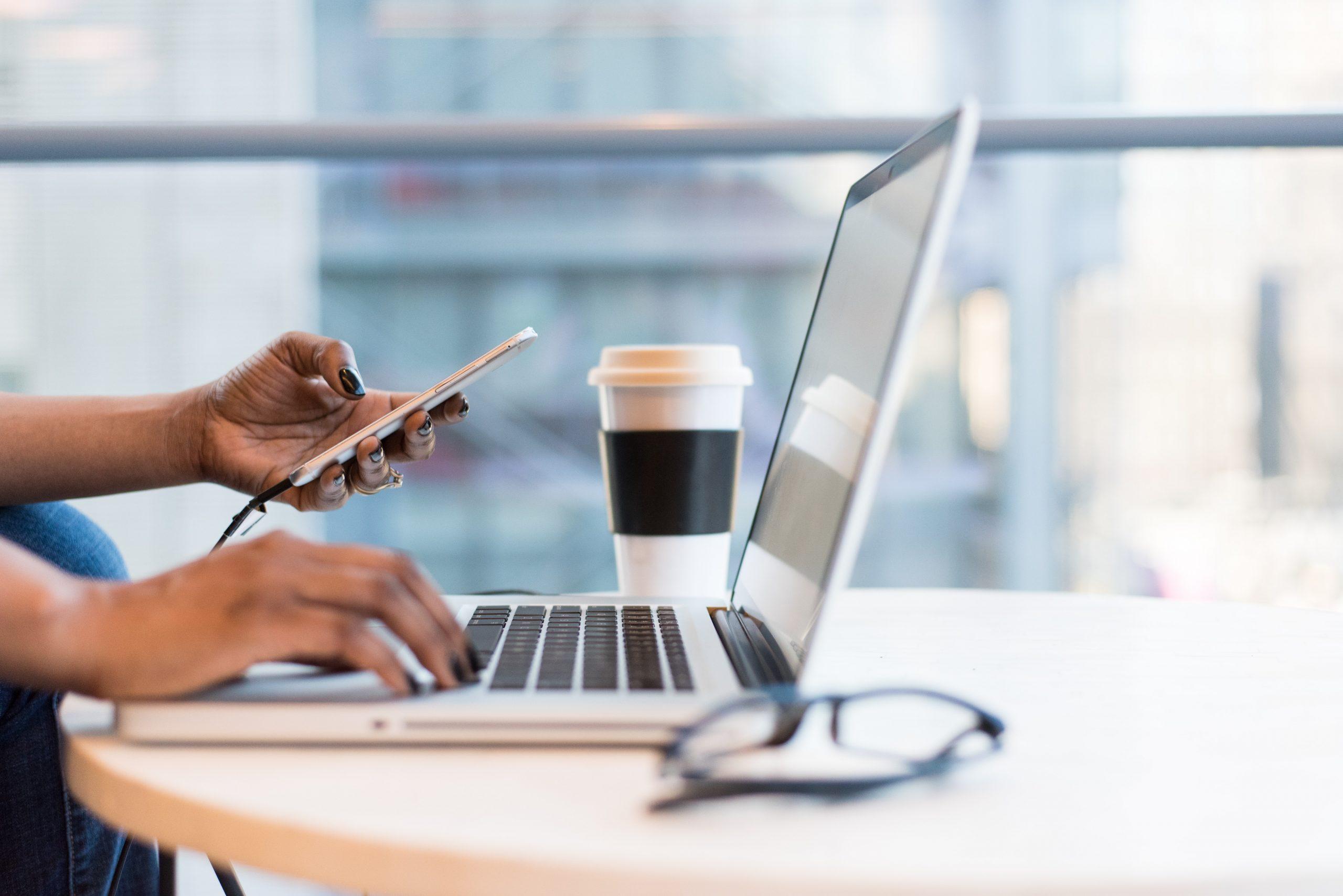 mão feminina usando computador e celular