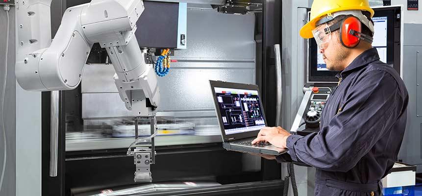 Engenheiro com notebook fazendo vistoria na máquina
