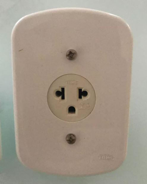 Tomada antigo padrão representando risco oculto em instalações elétricas antigas
