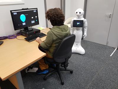 Aluno realizando teste com robô ao lado.