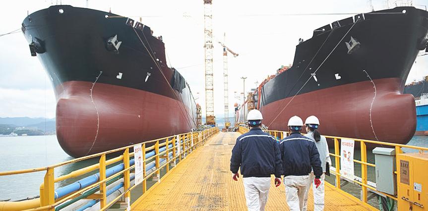 Engenheiros de uniforme azul andando no porto de navios representando áreas da engenharia