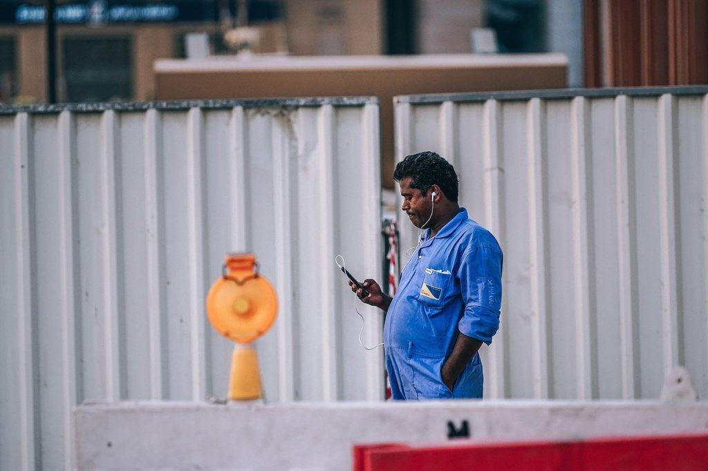 homem durante horário de trabalho, usando uniforme de cor azul e parado encarando celular