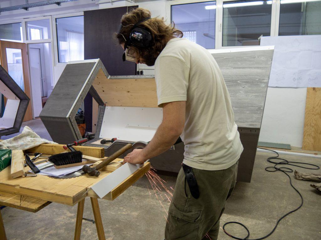 homem usando ferramentas para serrar madeira e construir a cápsula para desabrigados