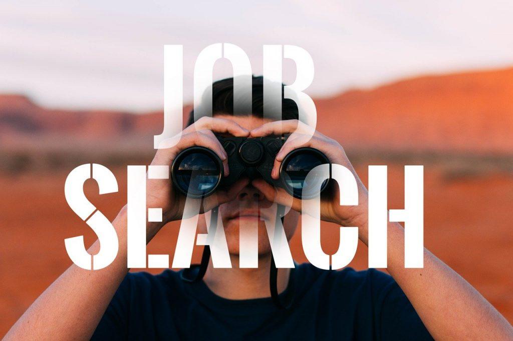 homem com binóculo representando a busca por emprego