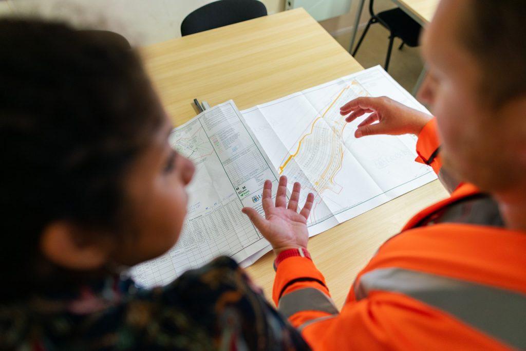 homem e mulher avaliando a planta de uma Construção Civil