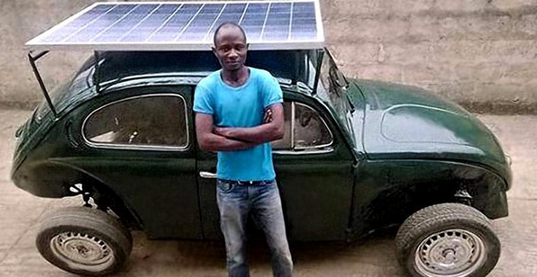 estudante nigeriano ao lado de seu fusca movido a energia solar