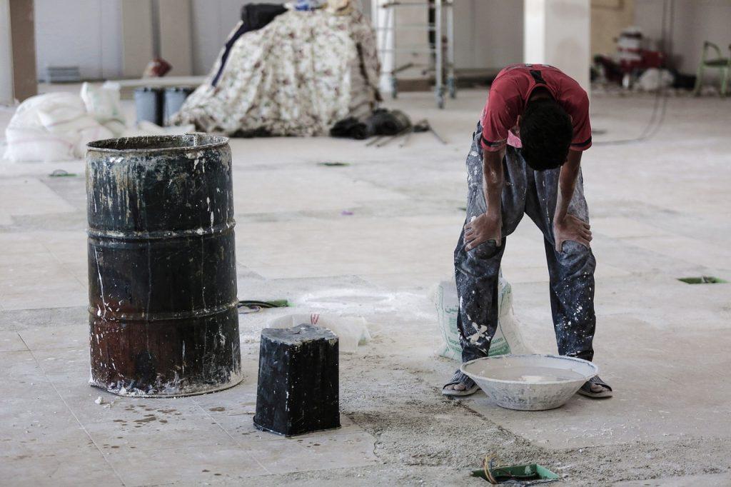 homem trabalhando em construção civil com a cabeça baixa, representando desânimo com o trabalho nessa área