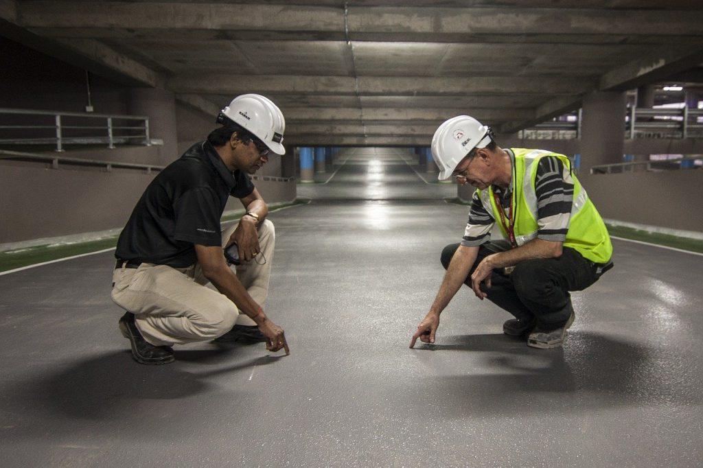 dois homens fazendo perícia em asfalto, ambos usando capacete
