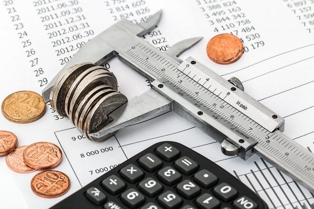 paquímetro, calculadora e moedas, representadno economia