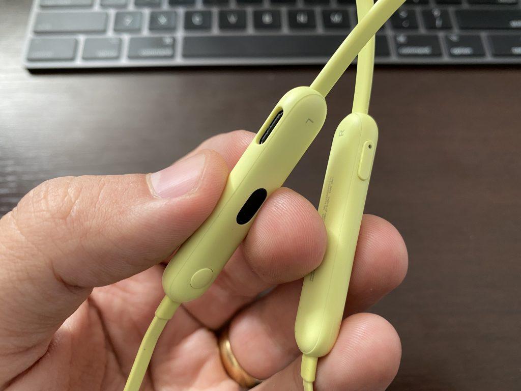 mão segurando fone de ouvido beat flex na cor amarelo