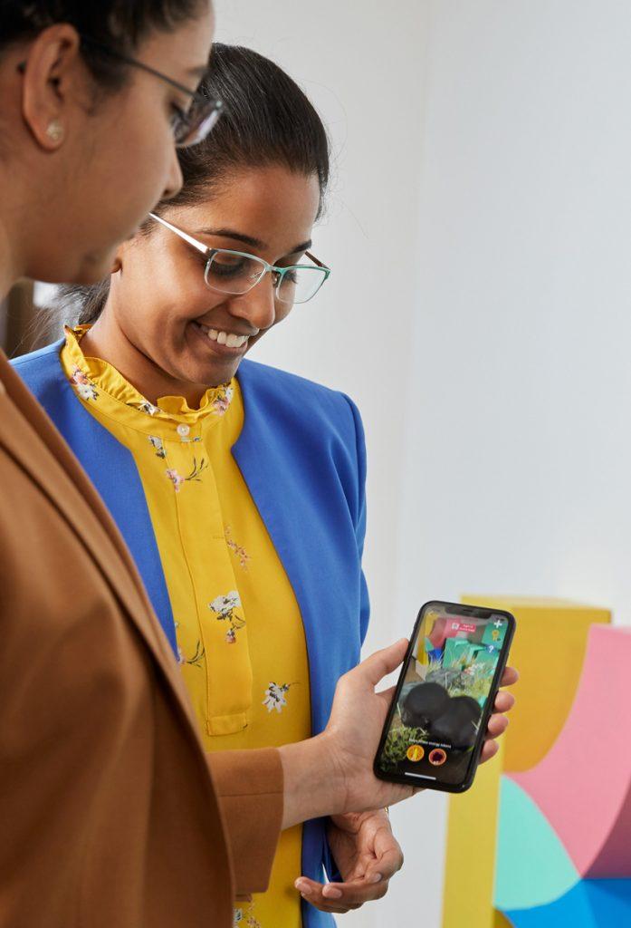 duas mulheres de lado com celular na mão, participando do Apple Entrepreneur Camp para mulheres