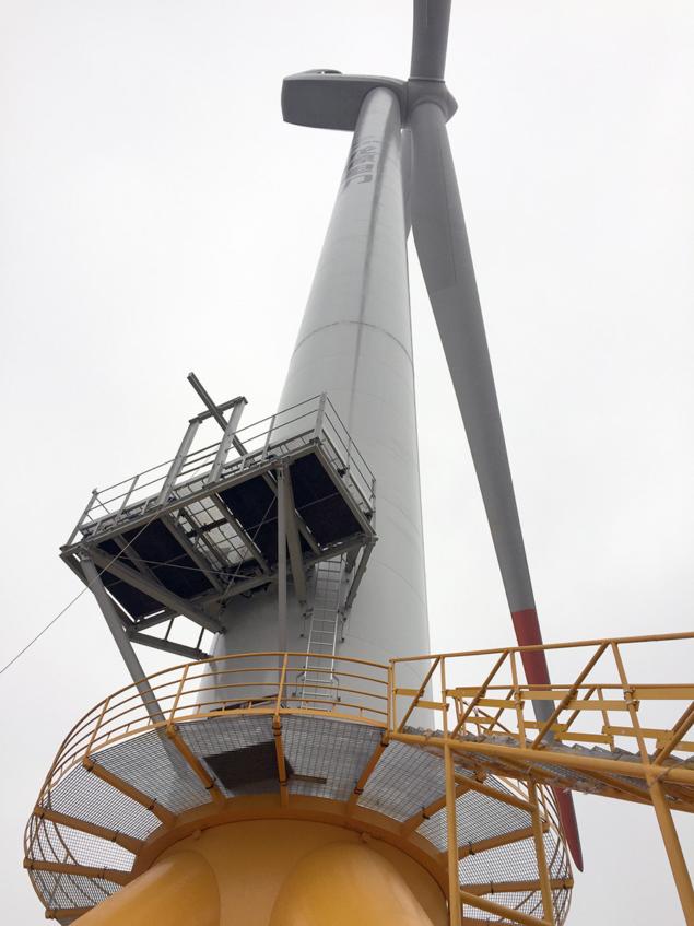 A imagem apresenta uma turbina de energia eólica vista debaixo