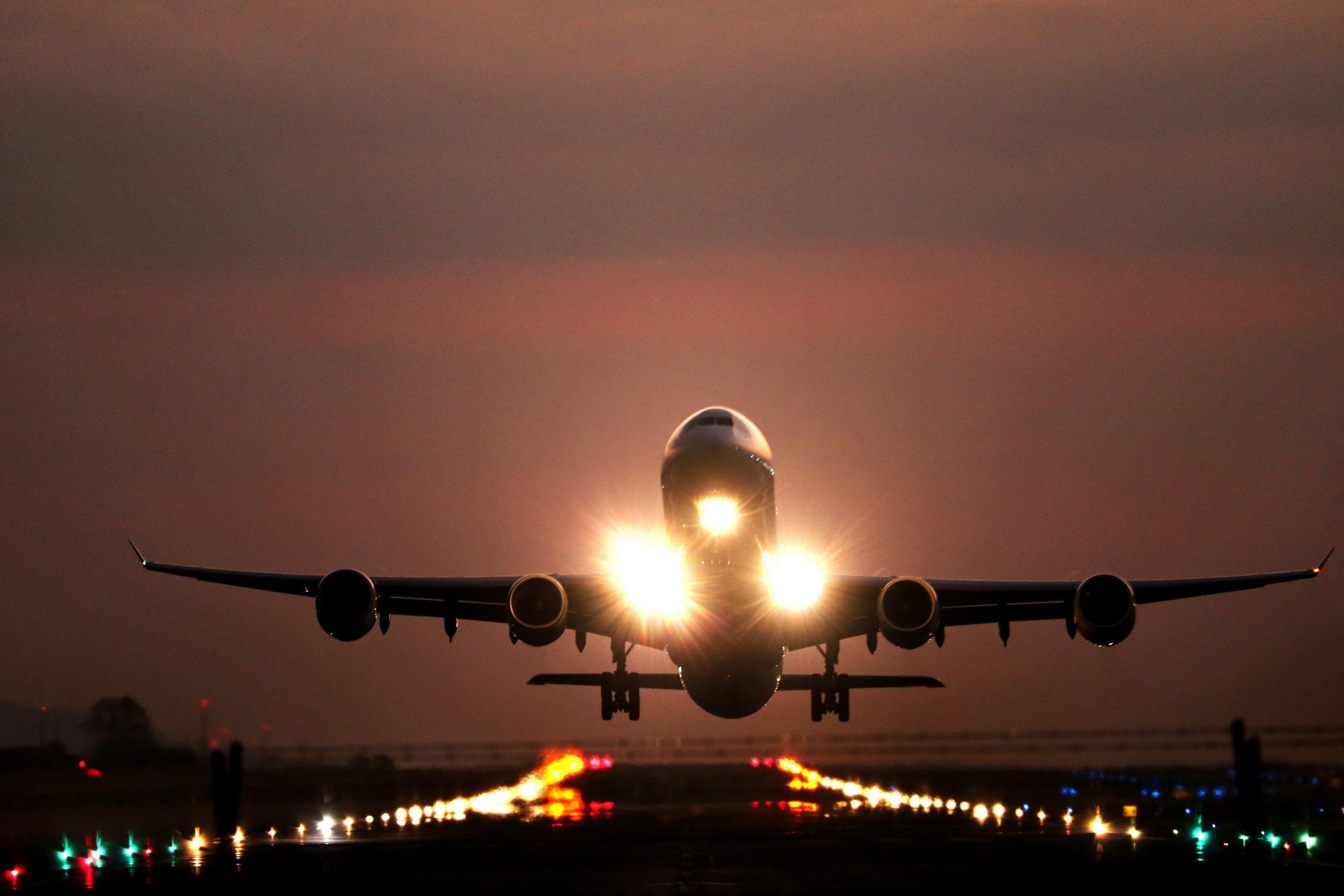 Avião pousando, e atrás um céu de entardecer