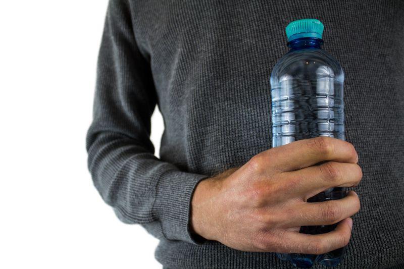 imagem de homem segurando à frente do corpo uma garrafa plástica - garrafas ecológicas