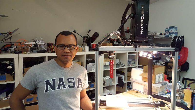 Fotografia de Fábio Teixeira, com camiseta escrito Nasa e na frente de instrumentos e caixas em escritório - Startup fundada por brasileiro cria nanosatélite que promete soluções para a agricultura